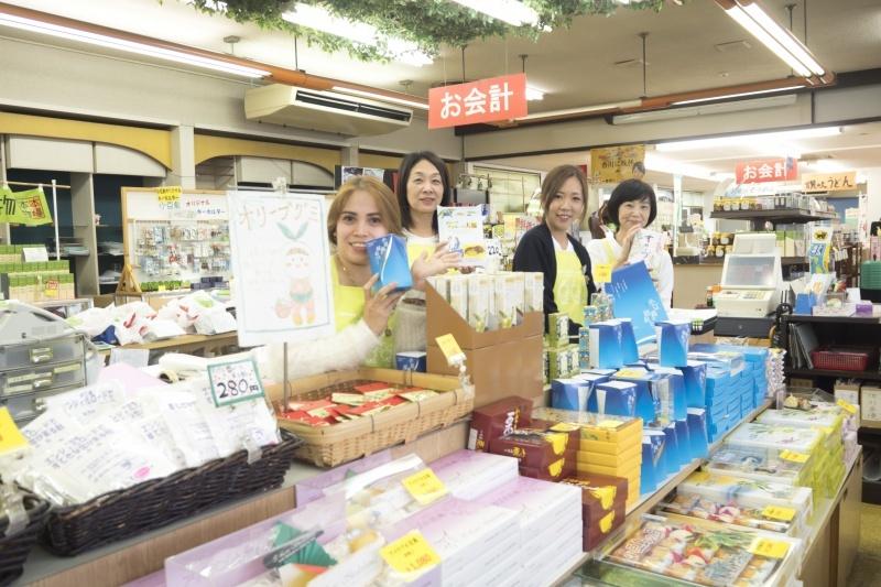 売り場で商品を手に笑顔な4人の女性